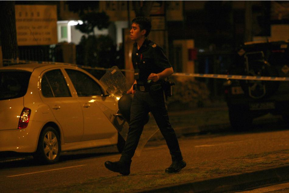 A police officer walks with a riot shield following a riot in Singapore's Little India district