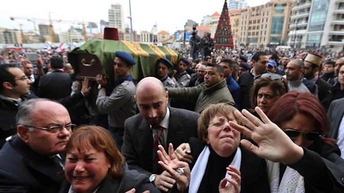 Relatives and friends of Mohammed Chatah, a senior aide to former Lebanese Prime Minister Saad Hariri, who was assassinated on Friday by a car bomb, weep as Lebanese people carry his coffin during his funeral procession at Martyrs' Square in Beirut, Lebanon, Sunday, Dec. 29, 2013. Angry mourners have chanted against Hezbollah as they buried the slain Lebanese politician who was critical of the Shiite militia. (AP Photo/Bilal Hussein)