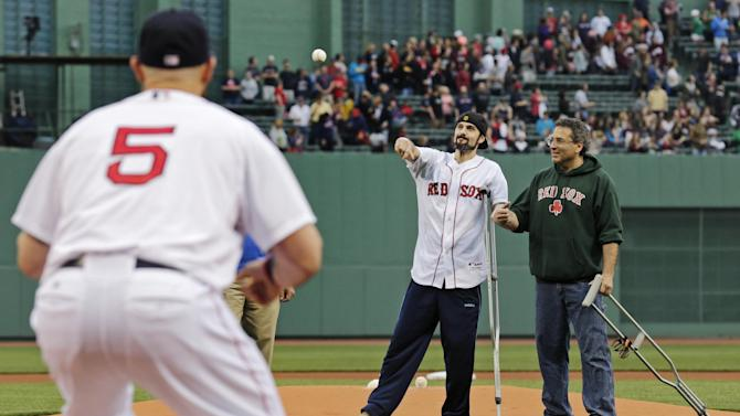 """In this Thursday, May 23, 2013 photo, Boston Marathon bombing survivor Pete DiMartino, of Rochester, N.Y., holds onto his dad, David, as he throws the ceremonial first pitch to Boston Red Sox left fielder Jonny Gomes (5) prior to a baseball game at Fenway Park in Boston. DiMartino was injured in an explosion near the finish line of the Boston Marathon. """"I don't want anybody feeling sorry for me,"""" he said. """"... I want people to see that this has made me a better person and I want people to become better people through what they see through me."""" (AP Photo/Charles Krupa)"""