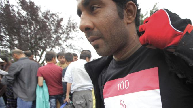 A migrant wearing a T-shirt reading '100% Hungarian' waits for a bus after crossing Austrian border in Nickelsdorf