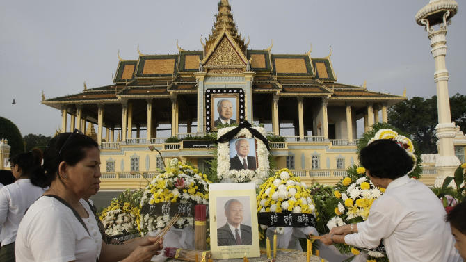 Cambodians burn incense stick as they offer prayers in front of the Royal Palace in Phnom Penh, Cambodia, Wednesday, Oct. 17, 2012. Cambodians continue to pray for the soul of their former King Norodom Sihanouk as the country prepared for the return of his body. (AP Photo/Heng Sinith)