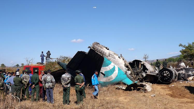 Myanmar officials and local residents observe a damaged Air Bagan plane crash-landed in Heho, Shan State, Myanmar, Tuesday, Dec. 25, 2012. An Air Bagan flight packed with Christmas tourists crash-landed on a road in central Myanmar on Tuesday, killing two people and injuring 11, officials said. Four foreigners were among the injured, state television reported. It said the fatalities included an 11-year-old passenger believed to be a Myanmar citizen and a man riding a motorcycle on the road where the plane came down. (AP Photo)