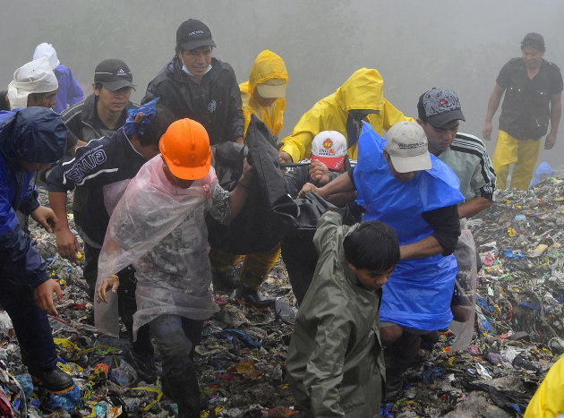 Rescuers and volunteers carry a body which they recovered from piles of garbage in Baguio City, northern Philippines, Monday, Aug. 29, 2011. Several tons of garbage buried some shanties after a dumpsi