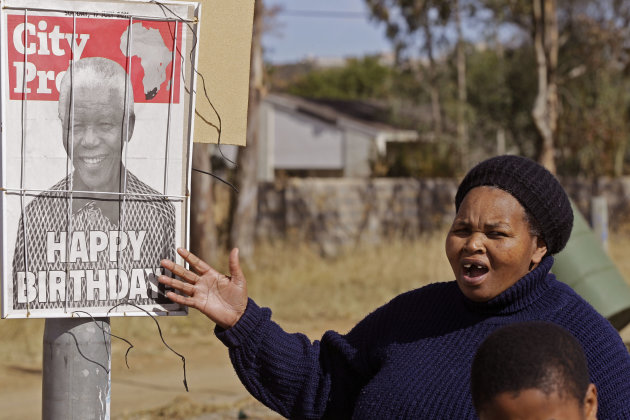 A woman reacts as she see a newspaper poster with a photo of former South African President Nelson Mandela  on it in  Mthatha, South Africa,  Sunday, July 17, 2011. Millions of South Africans will cel