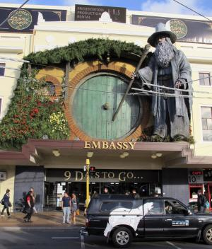 """People walk by the Embassy Theater where a giant statue of the character Gandalf from the upcoming movie """"The Hobbit: An Unexpected Journey"""" overlooks the passersby in Wellington, New Zealand, Monday, Nov. 19, 2012. Animal wranglers involved in the making of """"The Hobbit"""" movie trilogy say the production company is responsible for the deaths of up to 27 animals, largely because they were kept at a farm filled with bluffs, sinkholes and other """"death traps."""" (AP photo/Nick Perry)"""