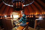 Organist Christopher Keady sits at the circular pipe organ at the Agnes Flanagan Chapel Tuesday, June 12, 2012, on the campus of Lewis & Clark College, in Portland, Ore. The Agnes Flanagan Chapel is a 16-sided architectural marvel that seats 650 under stained glass windows depicting the book of Genesis. In the early 1970s, it was also a big, conical quandary. Chapels arent really chapels unless they have an organ, and the newly-minted structure at Portlands Lewis & Clark College was in need. (AP Photo/Rick Bowmer)
