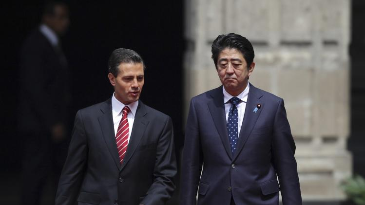 Mexico's President Enrique Pena Nieto and Japan's Prime Minister Shinzo Abe walk together while reviewing the honor guard at the presidential palace in Mexico City