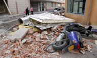 People walk near by the rubble in Lorca, Spain, on Thursday, May 12, 2011. Two earthquakes shook southeastern Spain in quick succession Wednesday, killing people, injuring dozens and causing extensive damage to buildings. It was the largest number of earthquake-related deaths in Spain over 50 years.