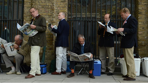 MCC members read newspapers as they wait in the queue outside the grounds before first test cricket match between England and New Zealand at Lord's cricket ground in London