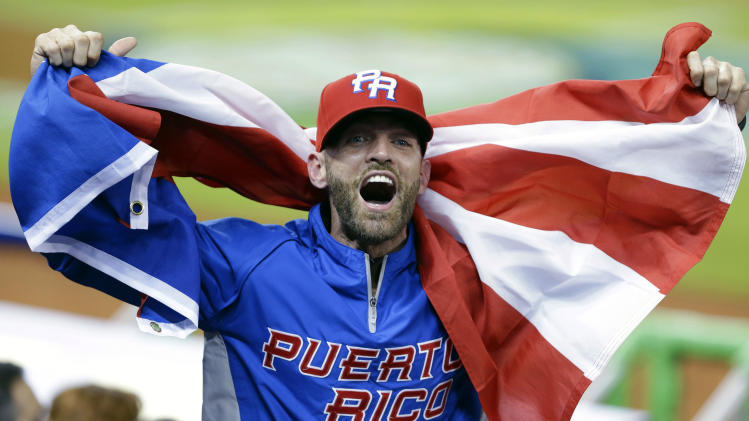 A Puerto Rico fan cheers during the seventh inning of the second-round elimination game of the World Baseball Classic against the United States, Friday, March 15, 2013, in Miami. Puerto Rico defeated the U.S. 4-3. (AP Photo/Wilfredo Lee)