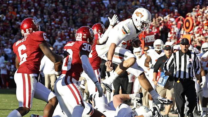 Oklahoma State quarterback Clint Chelf (10) leaps past Oklahoma defensive backs Demontre Hurst (6) and Javon Harris (30) during the second quarter of an NCAA college football game in Norman, Okla., Saturday, Nov. 24, 2012. (AP Photo/Sue Ogrocki)