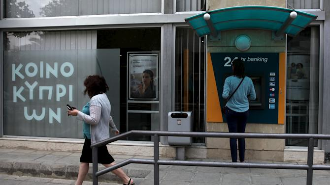 A woman withdraw money from ATMs at a branch of the Bank of Cyprus while another one walks by