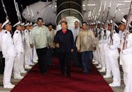 In this photo released by Miraflores Presidential Press Office, Venezuela's President Hugo Chavez, center, review the troops accompanied by his Foreign Minister Nicolas Maduro, left, and his Vice President Elias Jaua upon his arrival at the airport in Maiquetia, Venezuela, Saturday, July 23, 2011. Chavez made an unannounced return to Venezuela on Saturday night after spending a week in Cuba undergoing chemotherapy, saying that he expects a series of additional cancer treatments will take time. (AP Photo/Miraflores Presidential Office)