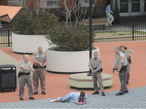 In this photo provided by John Fancher of the Tulsa City-County Library, sheriff's deputies surround a man who was wounded in an exchange of gunfire with law enforcement officers on the plaza in between the library and the Tulsa County Courthouse in Tulsa, Okla. on Wednesday, March 7, 2012. The shooter, a sheriff's deputy, and a bystander were wounded during the exchange, police said.