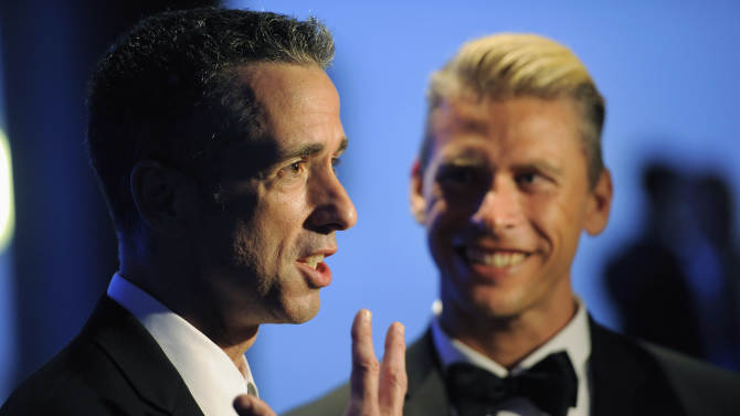 """FILE - In this Sept. 15, 2012 file photo, Dan Savage, left, and Terry Miller pose backstage with the Governors Award for the """"It Gets Better Project"""" at the 2012 Creative Arts Emmys at the Nokia Theatre in Los Angeles. A new Pediatrics study found scientific evidence that it does get better for gay teens, when it comes to bullying, although young gay men fare worse than their lesbian peers. (Photo by Chris Pizzello/Invision/AP)"""
