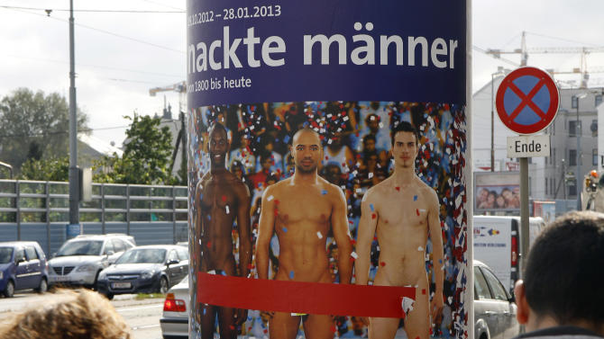 """In this picture taken Oct. 18, 2012 two people walk past a poster showing three naked men which has had red tape added to cover the sensitive parts of the three men, in Vienna, Austria. Poster reads: """"Naked Men"""". A prestigious Vienna museum, The Leopold Museum, has been forced to cover up a graphic poster advertising a new show devoted to male nudity, after protests that it is offensive. The show — """"Nude Men from 1800 to Today"""" — opened its doors Friday Oct. 20, looking at how artists have dealt with the theme of male nudity over the centuries. (AP Photo/Ronald Zak)"""