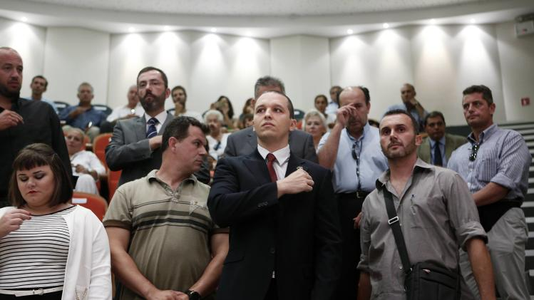 Golden Dawn lawmaker Kasidiaris, who is in custody pending trial, makes the sign of the cross during the Athens council swearing-in ceremony