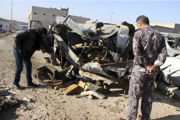 An Iraqi policeman looks at a damaged vehicle after a car bomb attack in Baghdad