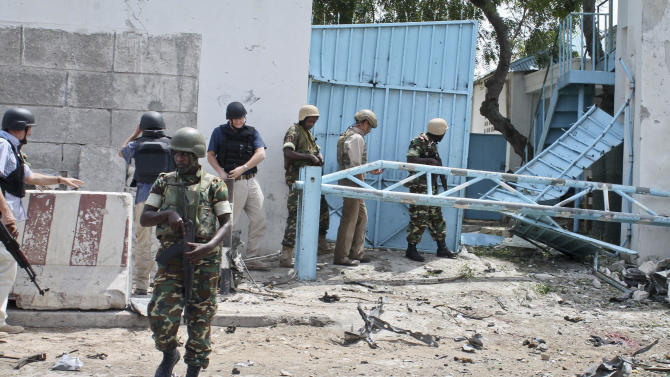 African Union peacekeepers and unidentified foreigners stand outside the main U.N. compound, following an attack on it in Mogadishu, Somalia Wednesday, June 19, 2013. Al-Qaida-linked militants detonated multiple bomb blasts and engaged in ongoing battles with security forces in an attempt to breach the main U.N. compound in Mogadishu, officials said Wednesday. (AP Photo/Farah Abdi Warsameh)