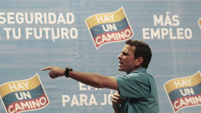 Venezuela's opposition presidential candidate Henrique Capriles speaks to a member of his campaign team during a news conference with foreign correspondents in Caracas, Venezuela, Monday, Oct. 1, 2012. Venezuela's presidential election is scheduled for Oct. 7. (AP Photo/Fernando Llano)