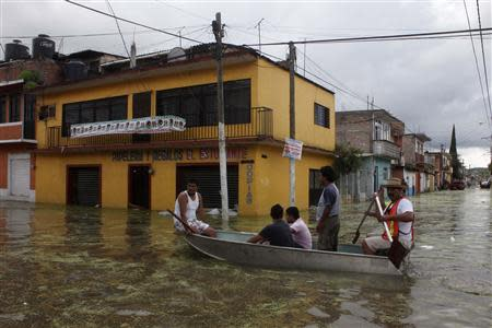 People ride a boat through a flooded street in Tixtla
