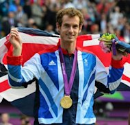 El escocs Andy Murray posa con la medalla olmpica correspondiente a los individuales masculinos de tenis, en el All England Tennis Club en Wimbledon, el 05 de agosto de 2012. (AFP | luis acosta)