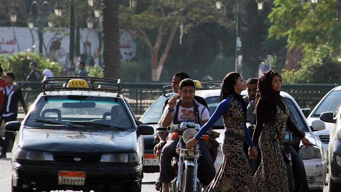 A youth on a motorcycle watches as young girls walk past near Cairo's Tahrir Square in this Sunday Oct 28 2012 photo. A group of Egyptian men had a mission for this year's Eid al-Adha, Islam's biggest holiday, which began Friday. They wanted to make some effort to stop sexual harassment of women, which in past years has spiked in Cairo during the holiday celebrations with the crowds of rowdy men in the streets. In past years, the Eid has seen major instances of harassment, with crowds of young men groping passing women — so heavily that women had to flee into shops, and for days afterward newspapers decried the mob attacks. (AP Photo/ Mohammed Abu Zeid)