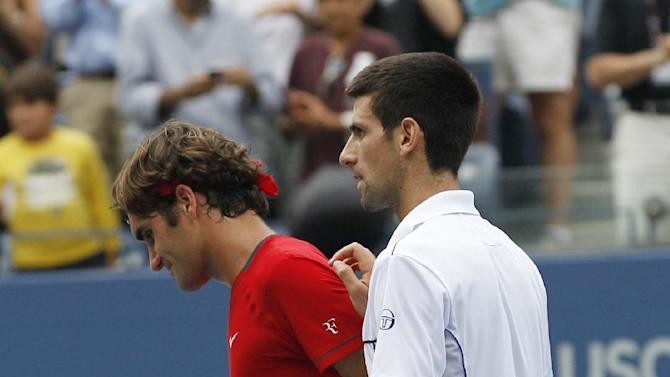 Roger Federer of Switzerland, left, and Novak Djokovic of Serbia, right, leave the court after a semifinal match at the U.S. Open tennis tournament in New York, Saturday, Sept. 10, 2011. (AP Photo/Elise Amendola)