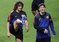 Barcelona's captain Carles Puyol (L) and Argentinian forward Lionel Messi attend a training session at Luz Stadium in Lisbon on the eve of their UEFA Champions League football match against Benfica