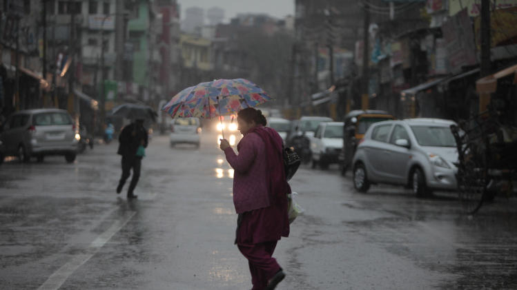 An Indian woman crosses a street as it rains in Jammu, India, Tuesday, March 11, 2014. The Kashmir valley was Tuesday cut off from rest of India due to heavy snowfall. (AP Photo/Channi Anand)
