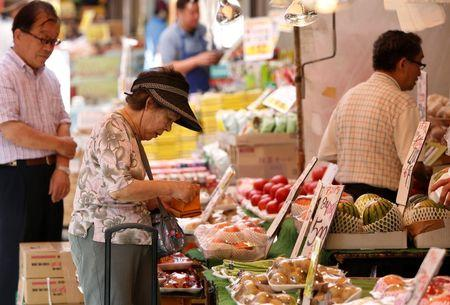 A woman rummages through her purse in front of a vegetable store in Tokyo