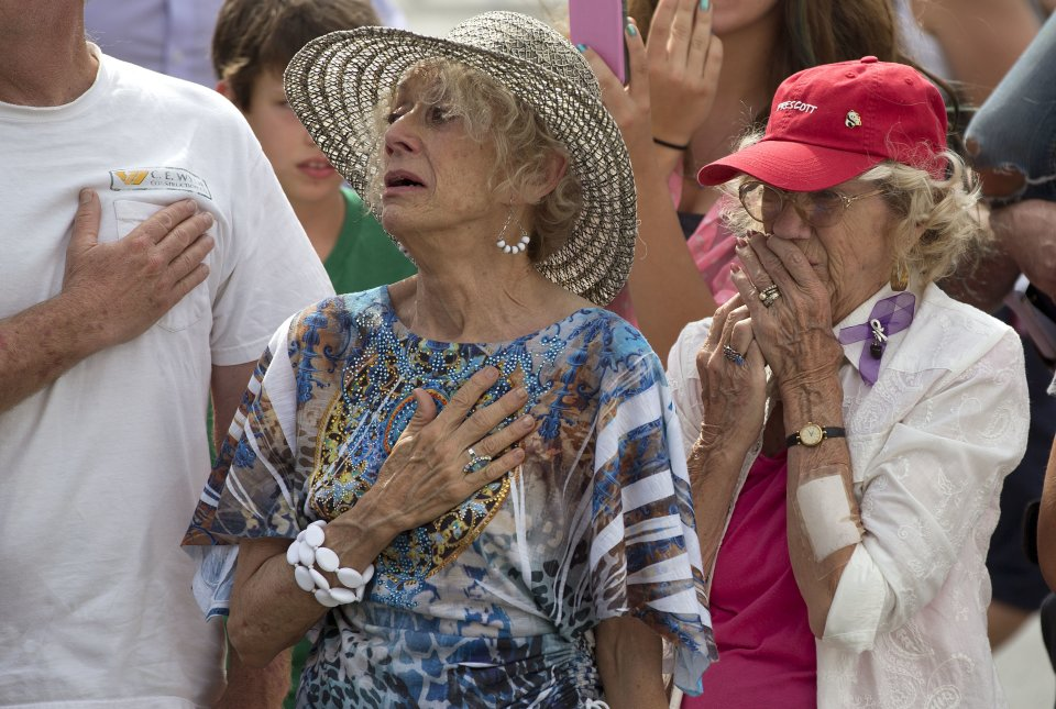 Two women react as as 19 hearses slowly roll by, Sunday, July 7, 2013 in downtown Prescott, Ariz., carrying the 19 Granite Mountain Hotshot firefighters killed a week ago by an out-of-control blaze near Yarnell, Ariz. The nearly five-hour-long procession began near the state Capitol in Phoenix, went through the town where the Granite Mountain Hotshots were killed and ended in the mountain community of Prescott, where they lived and will be laid to rest this week.(AP Photo/Julie Jacobson)