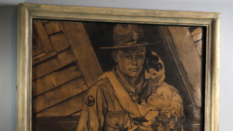 """Mary Immen Hall of Bennington, Vt., is reflected in the 1940 Norman Rockwell illustration """"A Scout is Helpful"""" for which she modeled at the Bennington Museum on Friday, Sept. 28, 2012, in Bennington, Vt. (AP Photo/Mike Groll)"""