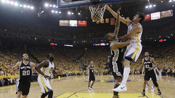 Golden State Warriors' Andrew Bogut, right, dunks over San Antonio Spurs' Boris Diaw, center, as the Warriors' Draymond Green (23) and the Spurs' Manu Ginobili (20) watch during the first half of Game 3 of a Western Conference semifinal NBA basketball playoff series in Oakland, Calif., Friday, May 10, 2013. (AP Photo/Jeff Chiu)