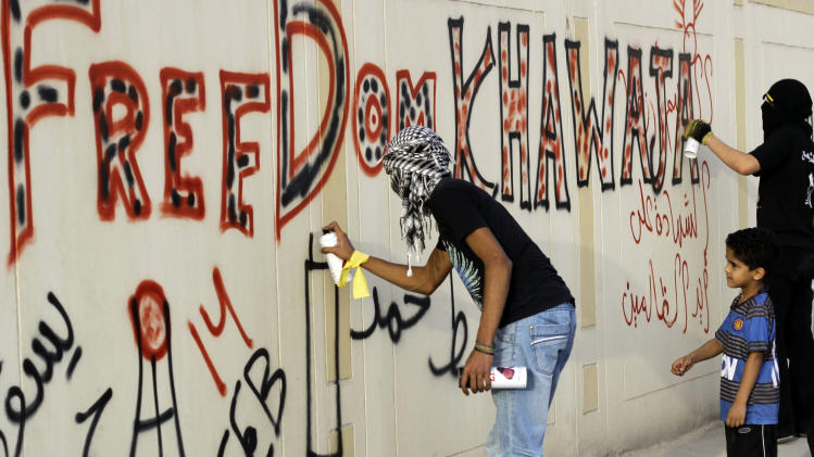 "Anti-government protesters spray graffiti on a wall in Sanabis, Bahrain, on Tuesday, April 24, 2012, calling for the release of jailed human rights activist Abdulhadi al-Khawaja, who has been on a hunger strike for more than 70 days. Witnesses said police in Bahrain have used tear gas and water cannons to disperse hundreds of protesters calling for al-Khawaja's release. Arabic on the walls reads: ""Down Hamad,"" referring to Bahrain's king, and ""Martyrdom at  the hands of the unjust."" (AP Photo/Hasan Jamali)"