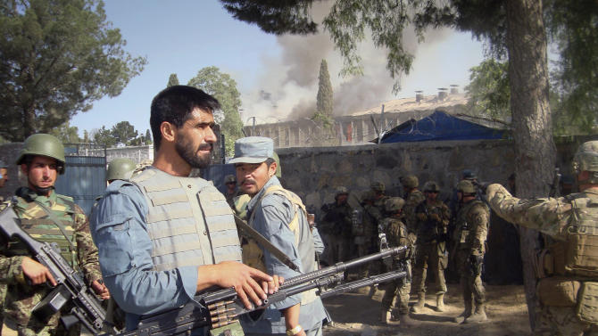 Afghan policemen, U.S. and Afghan soldiers on alert near the police traffic department building, which was under attack by insurgents in Khost, eastern of Afghanistan on Sunday, May 22, 2011.  Gunmen wearing police uniforms and suicide vests stormed a government building in eastern Afghanistan early Sunday, starting a running shootout with Afghan security forces who surrounded the compound, officials said. At least five people were killed in ongoing fight it as a fire raged through the structure. (AP Photo/Nishanuddin Khan)