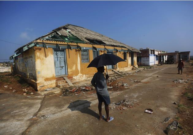 A man stands in front of a damaged house after Cyclone Phailin hit Gopalpur village