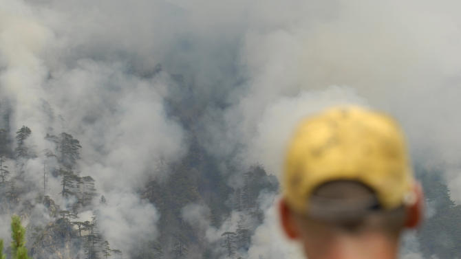 A Bosnian man looks at the raging wildfires near the Bosnian town of Konjic, 40 kms south of Sarajevo, Bosnia on Thursday, Aug 9, 2012. As firefighters tried to contain two wildfires near an ammunition factory in southern Bosnia on Thursday, one of the blazes began setting off explosions in a minefield left over from the country's war in the 1990s, officials said.  (AP Photo/Sulejman Omerbasic)