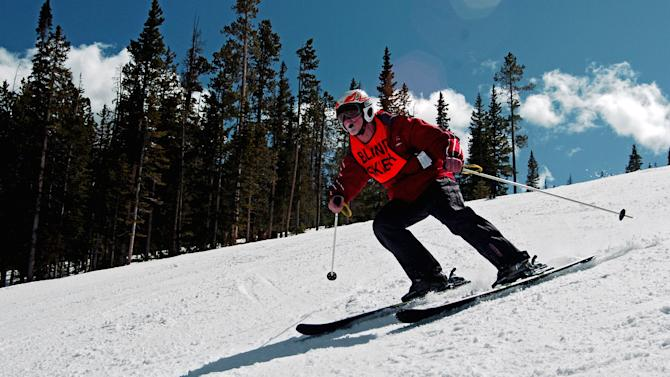 In this photo taken March 29, 2013, blind skier Vic Gurganious cruises down a run at Colorado's Winter Park resort. Gurganious, a member of the alpine ski team at the National Ability Center in Park City, Utah, says he reaches speeds of up to 60 mph while communicating with his guide via a two-way radio built into his helmet.(AP Photo/Thomas Peipert)