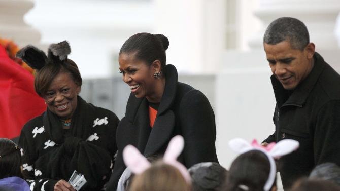 President Barack Obama, right, first lady Michelle Obama, center, her mother Marian Robinson, left, hand out Halloween treats as they welcome children from the Washington area and military members and their families to trick-or-treat at the White House in Washington, Saturday, Oct., 29, 2011. (AP Photo/Pablo Martinez Monsivais)