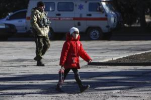 A girl walks across a square in the settlement of Velyka …