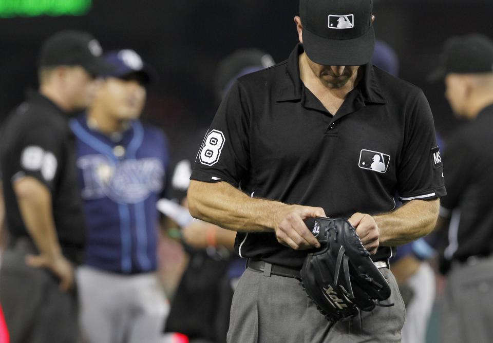 Umpire Chris Guccione leaves with the glove of Tampa Bay Rays relief pitcher Joel Peralta during the eighth inning of the Rays' baseball game against the Washington Nationals on Tuesday, June 19, 2012, in Washington. Peralta was ejected in the eighth inning for having a foreign substance on his glove. (AP Photo/Alex Brandon)