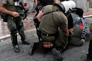 <p>Riot police detain a protestor in Athens during a demonstration against the visit of the German Chancellor Angela Merkel on October 9. EU leaders gather in Brussels for a summit Thursday on strengthening the bloc's shaky foundations as Spain appears set finally to ask for financial aid, easing a key eurozone pressure point.</p>