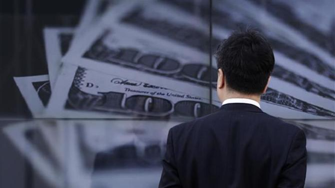 A businessman looks at a screen displaying a photo of U.S. 100 dollar bank notes in Tokyo April 8, 2013. REUTERS/Toru Hanai/Files