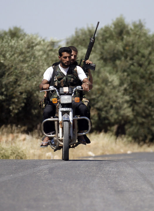 Armed Free Syrian Army soldiers ride a motorcycle on the outskirts of Idlib, Syria, Sunday, June 3, 2011. Free Syrian Army soldiers are determined to bring down the regime by force of arms, targeting