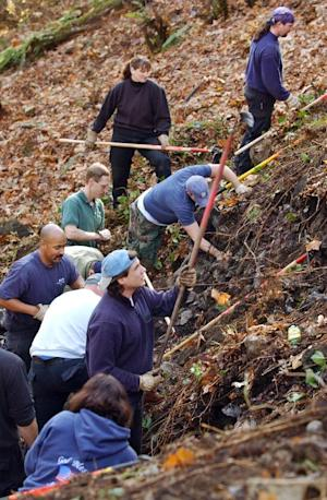 FILE - In this Nov. 12, 2003 file photo, members of the Green River task force comb a hillside in an unincorporated area near Kent, Wash. Serial killer Gary Ridgway says he might be able to locate the bodies of some of his Green River victims who were never found. (AP Photo/Elaine Thompson, File)