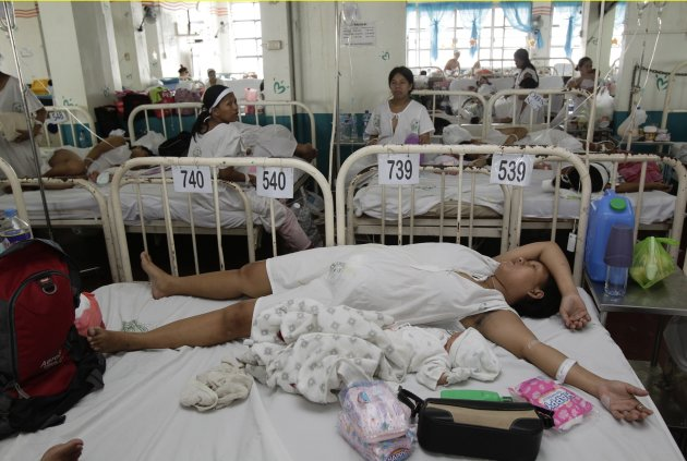 Mothers stay with their babies in tandem beds of four mothers and their babies at a ward normally occupied by around 300 mothers at one time, in Jose Fabella maternity hospital in Manila September 12, 2012. Pitting himself against the teachings of the country's powerful Catholic church, Philippine President Benigno Aquino, a Catholic like 80 percent of the population, has thrown his support behind a reproductive health bill that will, if passed, guarantee access to free birth control and promote sex education. Picture taken September 12, 2012.     REUTERS/Erik De Castro   (PHILIPPINES - Tags: POLITICS HEALTH SOCIETY POVERTY)  ATTENTION EDITORS: PICTURE 09 OF 27 FOR PACKAGE 'CONTRACEPTION, STATE AND CHURCH' SEARCH 'REPRODUCTIVE HEALTH' FOR ALL IMAGES