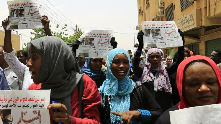 Journalists carry copies of the Al-Tayyar daily Sudanese newspaper as they protest against an attack on its Editor-in-chief Mirghani, in Khartoum