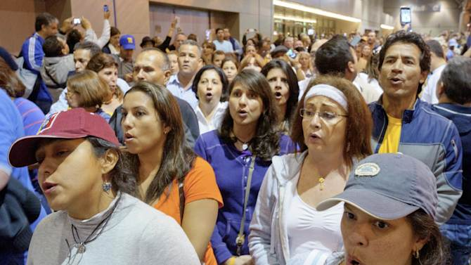 Venezuelan citizens living in the United States including Susana Guillen form Atlanta, bottom left, and Rosabla Cabello from Jackson, Miss. sing the Venezuelan national anthem as they wait to vote at the New Orleans Ernest Morial Convention Center, in New Orleans, Sunday, Oct. 7, 2012. Hundreds of Venezuelans living in the U.S. streamed into New Orleans on Sunday to cast ballots in the presidential election in their homeland, many of them determined to end the 13-year reign of Hugo Chavez. With the country's consulate in Miami closed, thousands of Venezuelans traveled by bus, car and plane to cast their votes at the consulate in New Orleans.  (AP Photo/Matthew Hinton)