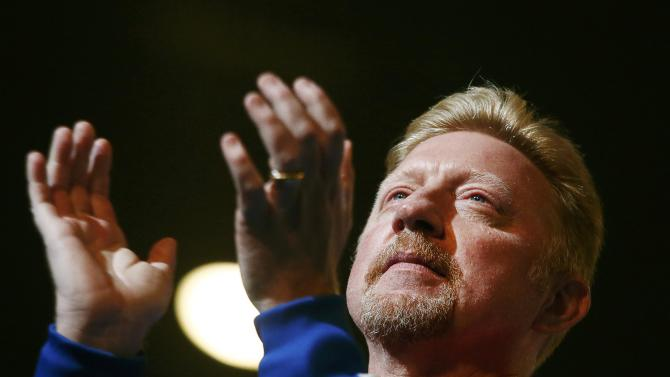 Becker, coach of Djokovic of Serbia, applauds as Djokovic receives his trophy following his win over Murray of Britain in their men's singles final match at the Australian Open 2015 tennis tournament in Melbourne